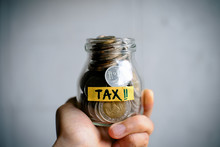 Hand Holding Money In A Jar With TAX Word On White Background. Financial And Tax Concept. Thai Bath Money In A Jar. The Glass Jar Full With The Coins