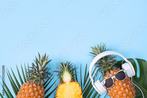 Photo Funny pineapple wearing white headphone, concept of listening music, isolated on colored background with tropical palm leaves, top view, flat lay design