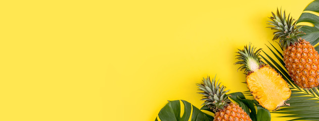 Beautiful pineapple on tropical palm monstera leaves isolated on bright pastel orange yellow background, top view, flat lay, overhead above summer fruit.