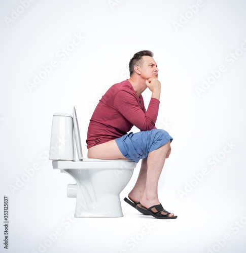 Vászonkép Man in sandals and casual clothes sits on the toilet and thinks while dreaming