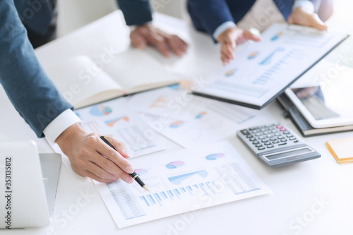 Fototapety, obrazy: Business people discussing with sales report calculating a data reference.