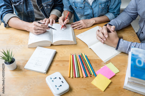 Leinwand Poster High school tutor or college student group sitting at desk in library studying a