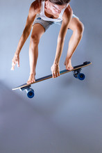 Skateboarder Doing Trick With Longboard In Front Of Grey Wall.