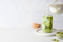 Iced Green Matcha Latte Tea And Pouring Milk In Glass On White Background.Close Up. Horizontal Orientation.