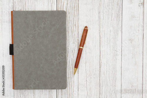 Leather book with pen on weathered whitewash wood background with grain texture Fototapeta