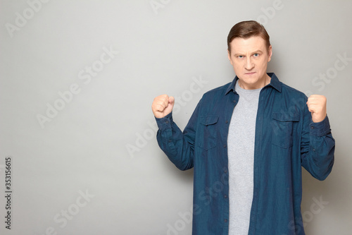 Portrait of angry dissatisfied mature man raising clenched fists up Canvas-taulu