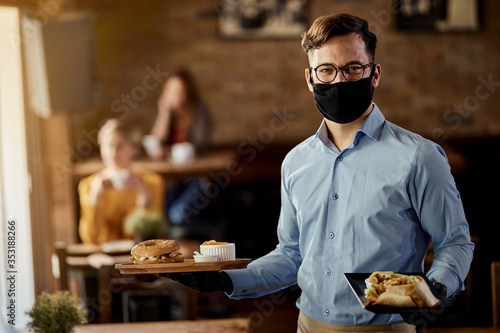 Obraz Happy waiter serving food while wearing protective face mask in a pub. - fototapety do salonu