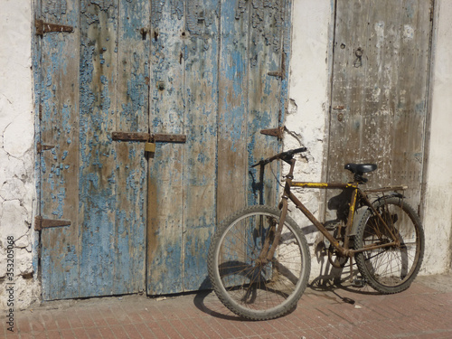 Bicycle leaning against weathered wooden door with lock © Chrissie