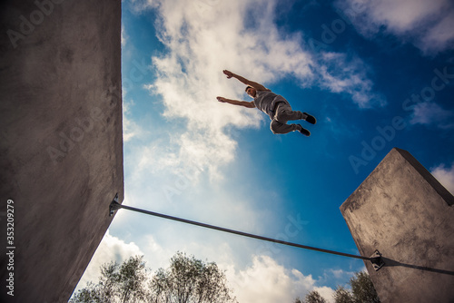 Fotografie, Obraz Man engaged in parkour jumping on the street workout