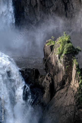 High angle shot of a beautiful waterfall near a rocky cliff covered with trees