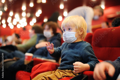 Fototapeta Cute toddler boy wearing face mask watching cartoon movie in the cinema after quarantine. Lifting virus lockdown. Social distancing restrictions remain. obraz