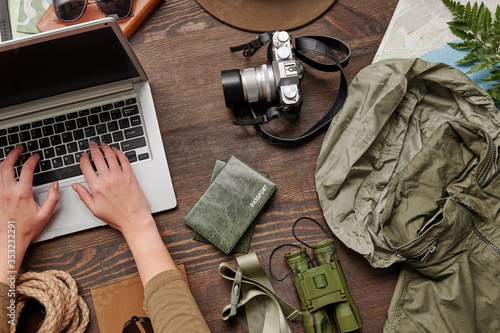 Fototapeta Above view of unrecognizable woman using laptop while buying airline tickets online and planning hiking trip, flat lay obraz