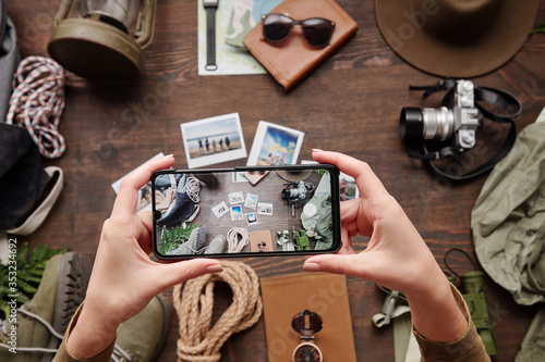 Fototapeta Above view of unrecognizable hiker using smartphone while photographing travel composition on table obraz