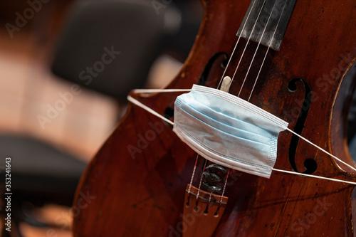 A face mask put over the bridge of a cello representing performance restrictions Billede på lærred