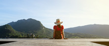 Girl With A Stalk Hat On And Red Dress Looking At The Mountains With Her Shoes On A Dock By A Lake