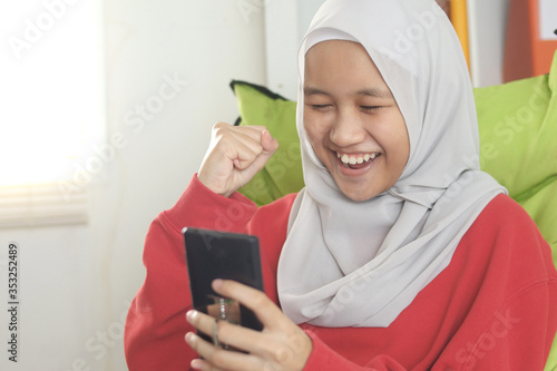Muslim girl laughing happily when reading good news on her phone, excited awe wi Canvas Print