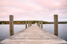 Deserted Wooden Pier On A Lake With Forested Shores At Dusk. Beautiful Fall Foliage. Lake Winnipesaukee, NH, USA.
