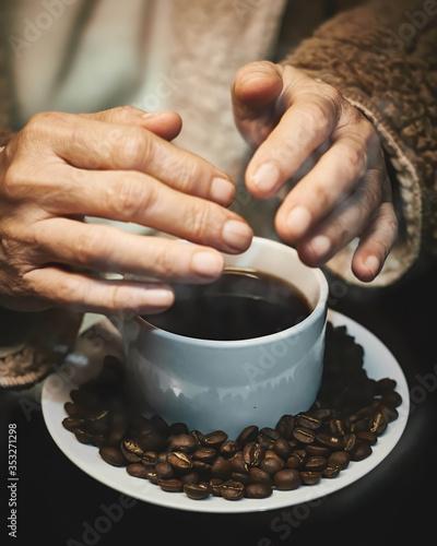 Manos de mujer adulta calentandose sobre una taza de cafe caliente con granos tostados alrededor sobre un plato blanco redondo y fondo negro Canvas Print