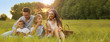 Leinwandbild Motiv Happy family having picnic and blowing soap bubbles in park at sunset, space for text. Banner design
