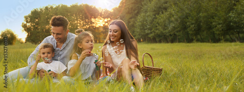 Happy family having picnic and blowing soap bubbles in park at sunset, space for text Fotobehang