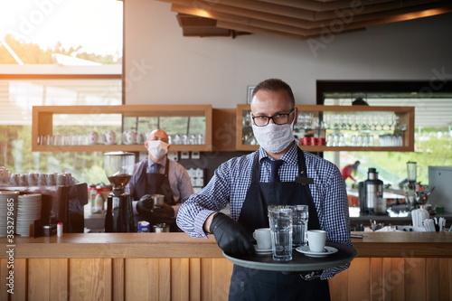 Fototapeta waiter in a medical protective mask serves  the coffee in restaurant obraz