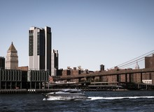 View Of Tall Buildings In New York City With A Yacht Travelling Across The River