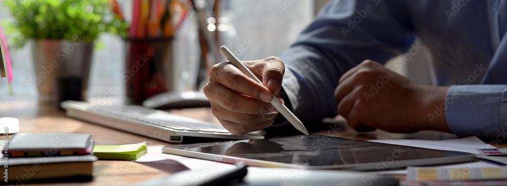 Fototapeta Close up view of graphic designer drawing on digital tablet on wooden worktable