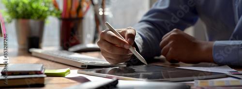 Fotografie, Obraz Close up view of graphic designer drawing on digital tablet on wooden worktable