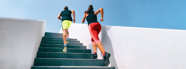 Stairs running up couple athletes runners running up staircase exercising cardio with hiit interval training workout. Fitness gym active sport people climbing in urban city panoramic banner.