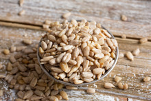 A Closeup View Of A Bowl Filled With Sunflower Seed Kernels, On A Wooden Table Surface.