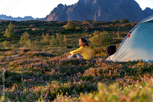 Obraz A young woman in yellow  jacket sits next to a camping tent on the background of a beautiful landscape at sunset, traveling to Norway Lofoten islands - fototapety do salonu