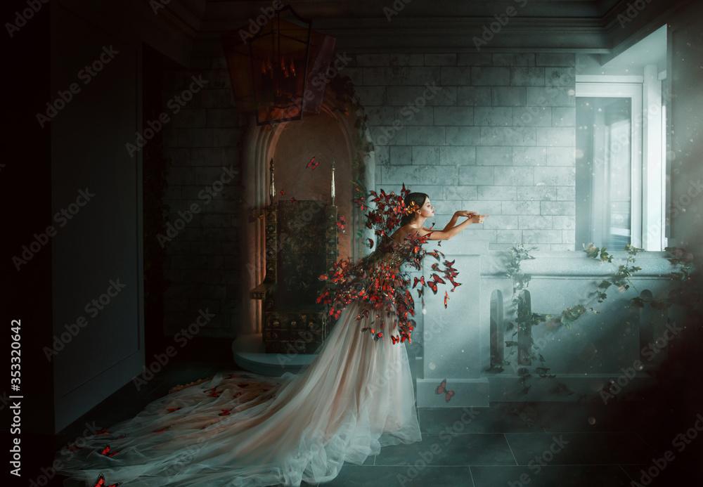 Fototapeta Artwork photo. Image gothic queen. black orange monarch butterflies. Dark room of castle, golden throne, magic sun rays from window. Creative dress Long train peach silk skirt. Glamour fantasy woman
