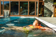 Little Girl Playing In Outdoor Swimming Pool Of Luxury Spa Alpine Resort In Alps Mountains, Austria. Winter And Snow Vacation With Kids. Hot Tub Outdoors With Mountain View. Children Play And Swim.