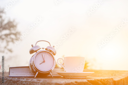 A white coffee cup and an alarm clock are placed beside the Bible on a wooden table in the morning to prepare for Bible study and watch the beautiful scenery in the morning after drinking coffee Canvas Print