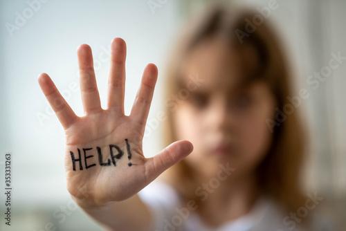 Photo Little girl asks for help, help written on hand