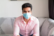 Young Indian businessman with mask for protection from corona virus outbreak staying at home under quarantine