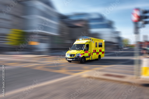 Ambulance responding to emergency call driving fast on street
