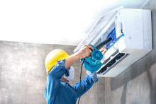 Technician Man Repairing ,cleaning And Maintenance Air Conditioner On The Wall With Blower In Bedroom Or Office Room.On Site Home Service,Business ,Industrial Concept.