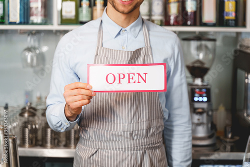 Fotografía Young man in apron holding open sign