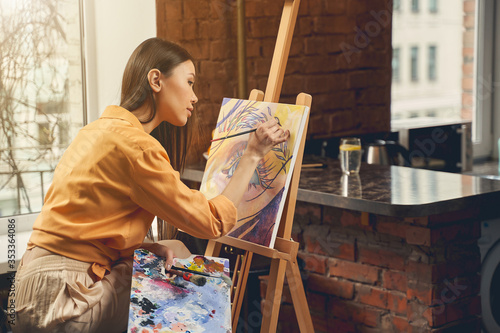 Pretty lady painting beautiful picture on easel at home Canvas Print