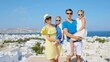 Family vacation in Europe. Parents and kids background the old town in Mykonos island, Greece