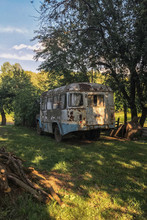 Old Rusty Soviet Bus In A Wild Forest With An Abandoned House