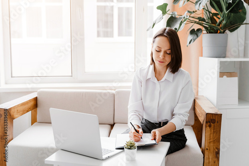 Obraz Young businesswoman working in office. Business and freelance concept. - fototapety do salonu
