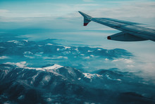 Airplane Wing Over Snowy Mountains In Switzerland