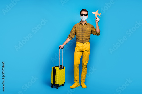 Obraz Full length body size view of nice guy wearing gauze mask gumshoes traveling abroad airplane open border quarantine enjoy business class isolated bright vivid shine vibrant blue color background - fototapety do salonu