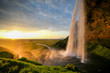 Waterfall Selandjafoss Iceland at sunset or sunrise. Beautiful waterfall in Iceland. Golden hour. Cave and waterfall. Travel in Iceland. Beautiful sky against the big waterfall. inside the water.