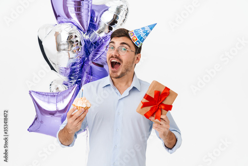Photo of excited caucasian man in party cone holding cake and gift box