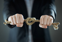 The Businessman's Hands Tighten The Rope Knot Against Background Of Suit In Blur.