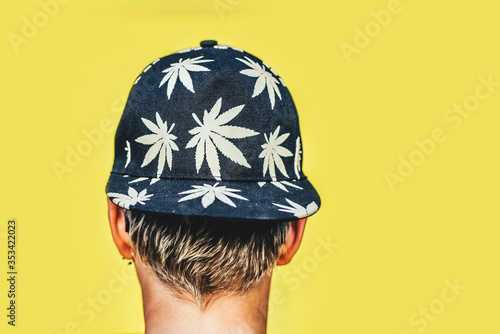 Young girl in sunglasses and cap with leaves of marijuana smokes on a yellow wall background Canvas Print