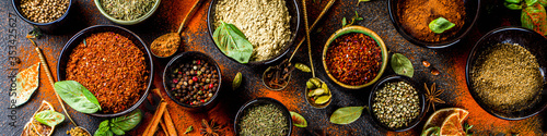 Obraz Set of Spices and herbs for cooking. Small bowls with colorful  seasonings and spices - basil, pepper, saffron, salt, paprika, turmeric. On black stone table top view copy space - fototapety do salonu